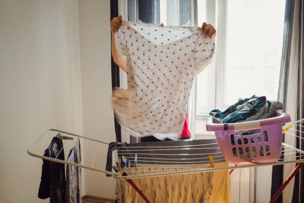 Woman in action A woman is putting her clothes dry. She is not visible from the t-shirt. wet clothing women t shirt stock pictures, royalty-free photos & images