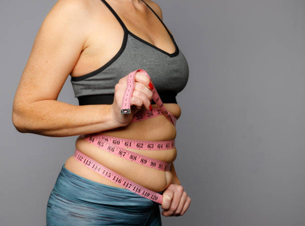 Woman in Active Wear With Squeezed Measuring Tape on a Gray Background stock photo