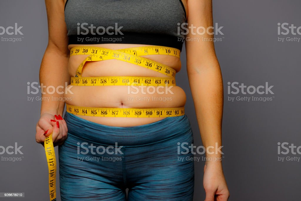 Woman in Active Wear With Squeezed Measuring Tape on a Gray Background - Foto stock royalty-free di Addome