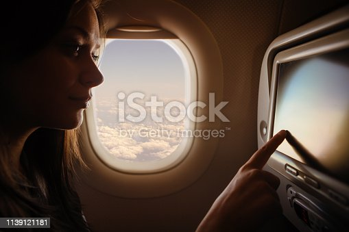 Woman using the touch screen on the airplane