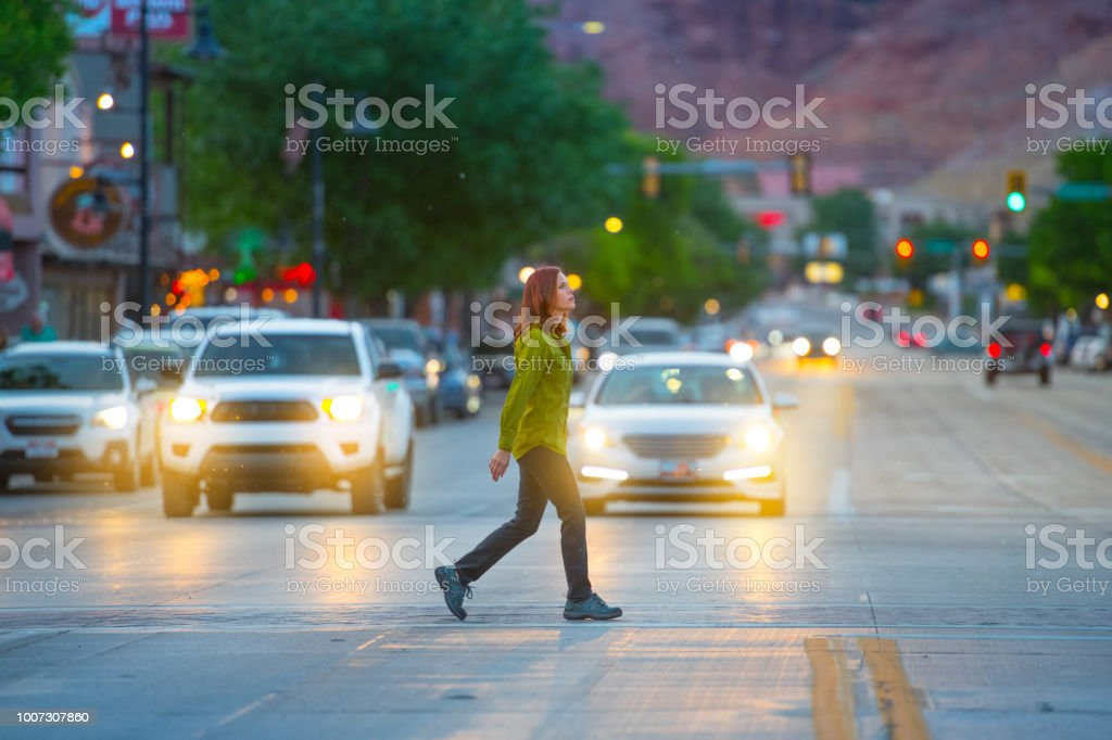 Woman in american small city traffic crossing road, mountains in...