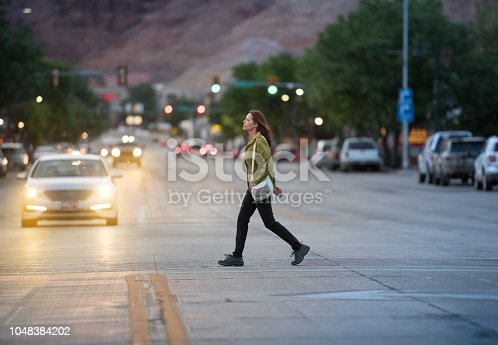 Woman in american small city traffic crossing road, mountains in background