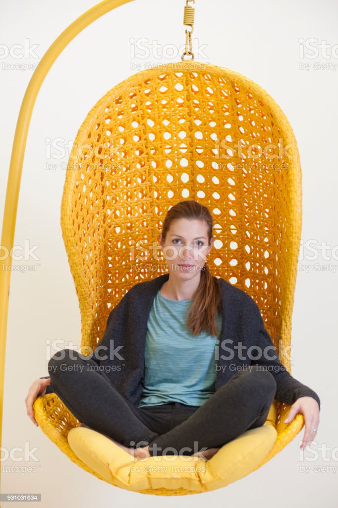 Woman in an creative office hanging chair stock photo