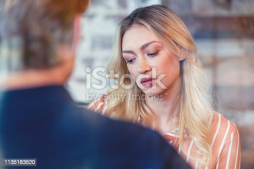 Woman in an interview. She is looking sad and upset. She could be talking to a mental health doctor, or in a job interview. She is looking down