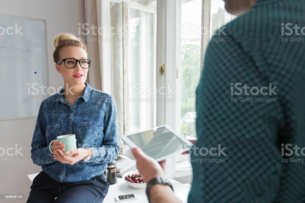 Woman in an office with cup of coffee Blonde woman wearing jeans shirt and nerd glasses in an office, holding cup of coffee and talking with her colleague. Man using a digital tablet.  2015 Stock Photo