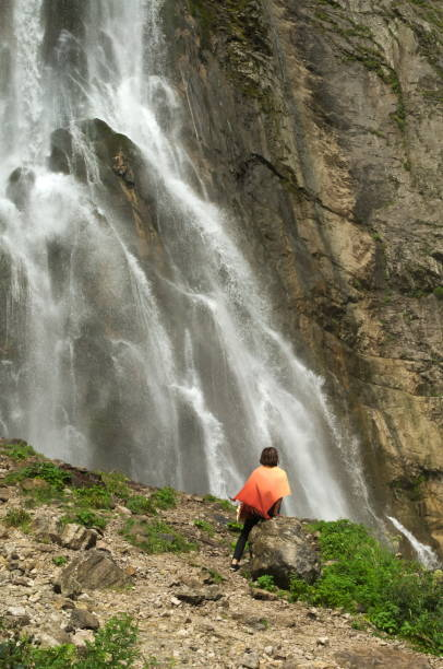 Woman in an orange stole sits near a waterfall stock photo