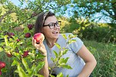Woman in an sun apple orchard holds red ripe apple in her hand, copy space. Harvest, autumn, organic natural healthy food, gardening, fruits, people concept