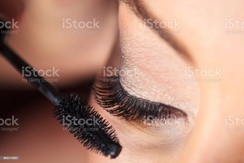 A woman in applying mascara stock photo