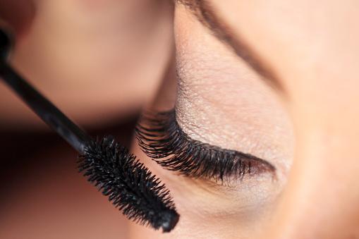 A Woman In Applying Mascara - Fotografie stock e altre immagini di Accudire