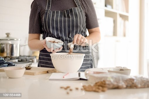 Shot of woman wearing apron adding cocoa powder in bowl at kitchen counter.
