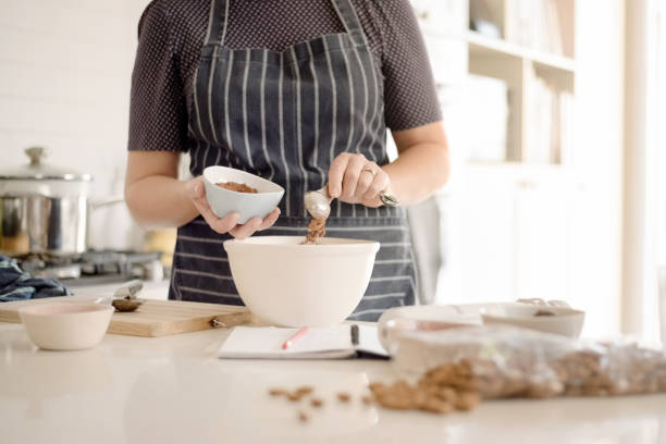 Woman in apron adding cocoa powder to the batter in bowl. Shot of woman wearing apron adding cocoa powder in bowl at kitchen counter. mixing stock pictures, royalty-free photos & images
