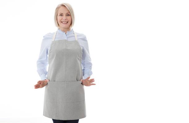 Mujer en delantal. Mujer llena de confianza en delantal manteniendo los brazos cruzados y sonriendo mientras está de pie contra el fondo blanco - foto de stock