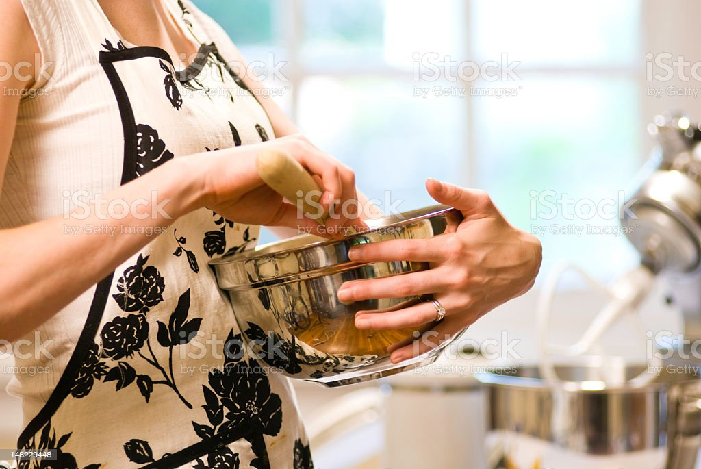 Woman in apron holding stainless steel mixing bowl stock photo