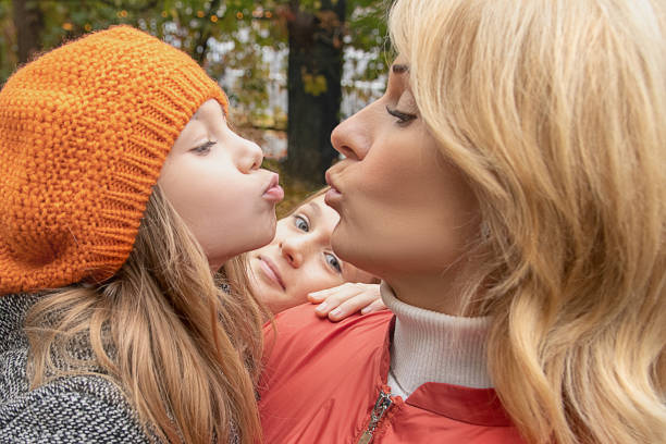 woman in autumn clothes have fun with cute child baby girl and teen girl. mother, little kid daughter in garden outdoors. mother's day love family, parenthood childhood concept. close-up photo. - kids kiss embarrassed foto e immagini stock