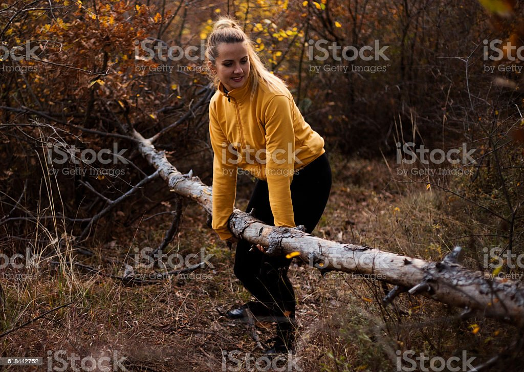 Woman in autumn forest is trying to remove fall free. stock photo
