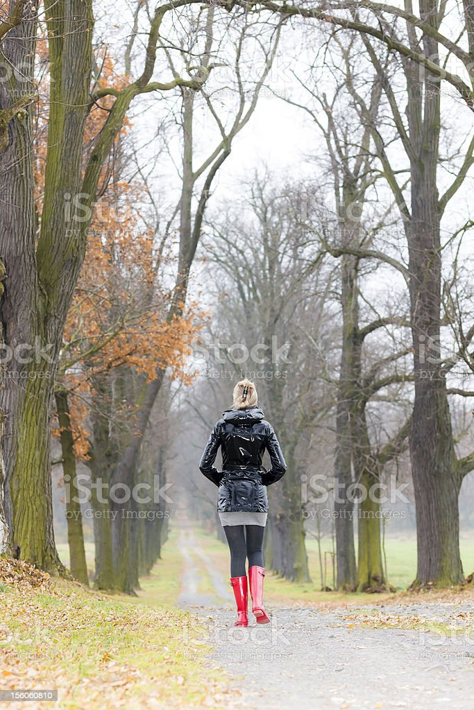 woman in autumnal alley royalty-free stock photo