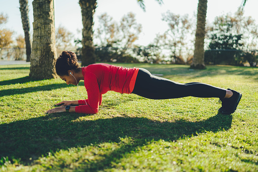 Mixed race sportswoman doing plank exercise in the park