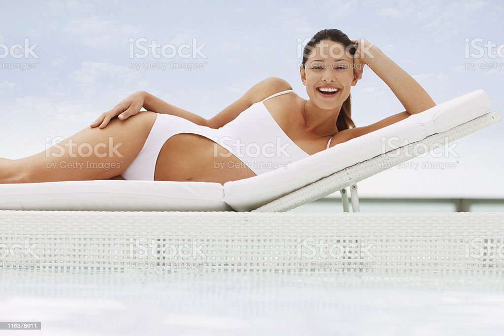 Woman in bathing suit laying on lounge chair at poolside stock photo