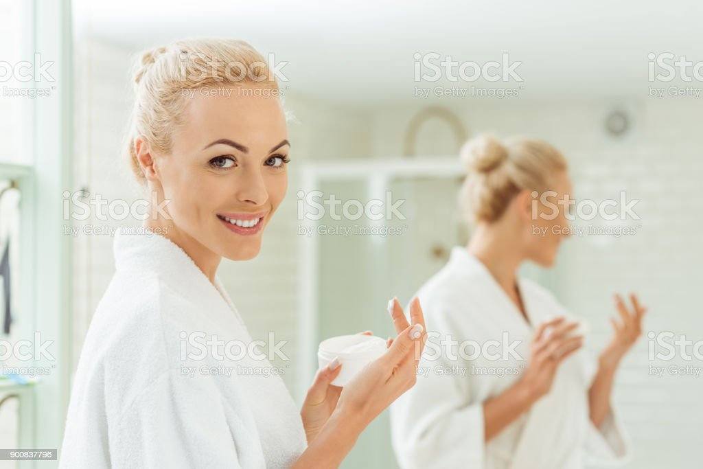 woman in bathrobe applying face cream - foto stock