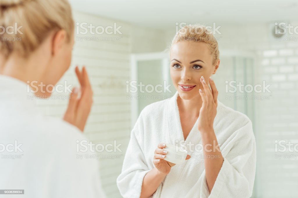woman in bathrobe applying face cream stock photo