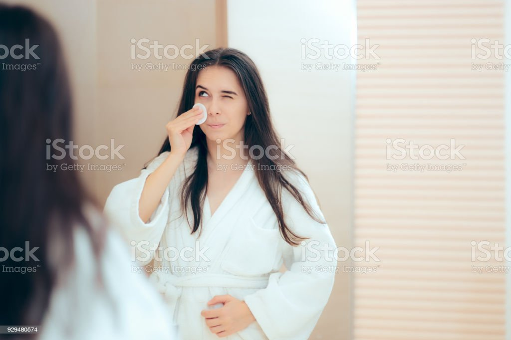 Woman in Bathrobe Cleaning Her Face with Make-up Remover stock photo