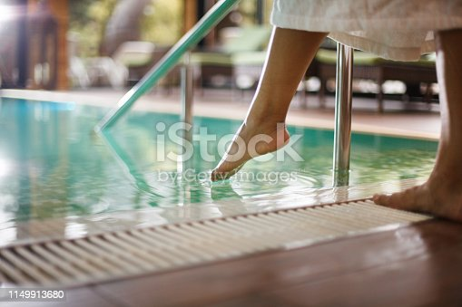Low section of a woman dipping toes into swimming pool at spa.