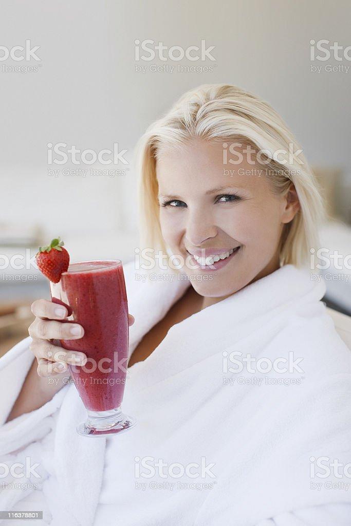 Woman in bathrobe drinking fruit smoothie royalty-free stock photo