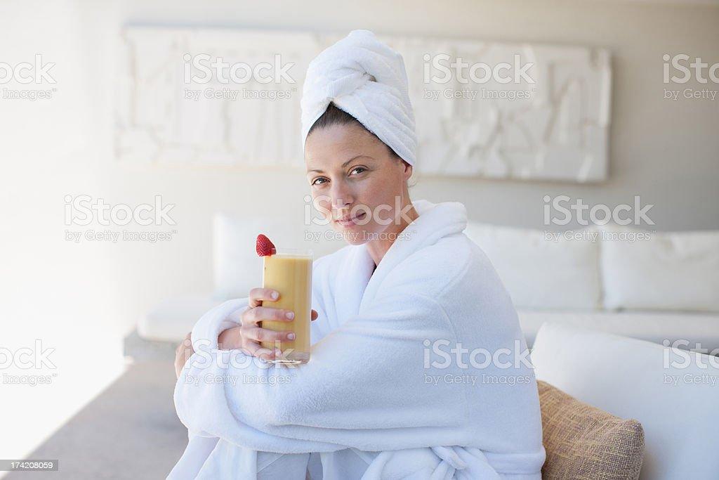 Woman in bathrobe drinking smoothie royalty-free stock photo