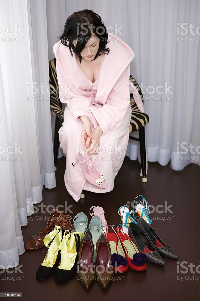 Woman in bathrobe looking at shoes collection royalty-free stock photo