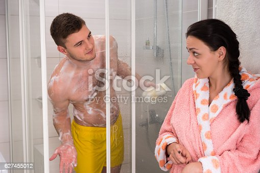 536952169 istock photo Woman in bathrobe points to husband that it's her turn 627455012