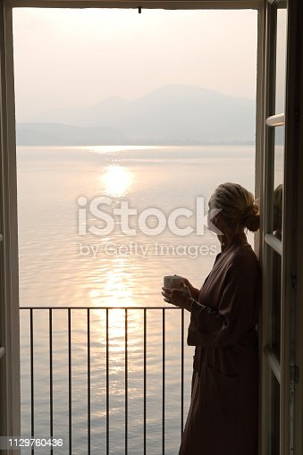 She looks off to distant scene and holds hot beverage