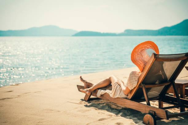 frau im strandstuhl - sun chair stock-fotos und bilder