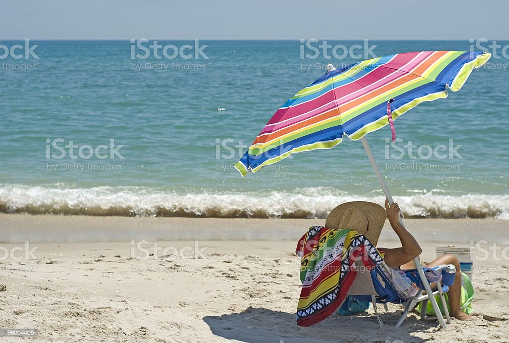Woman in Beach Chair with Umbrella royalty free stockfoto
