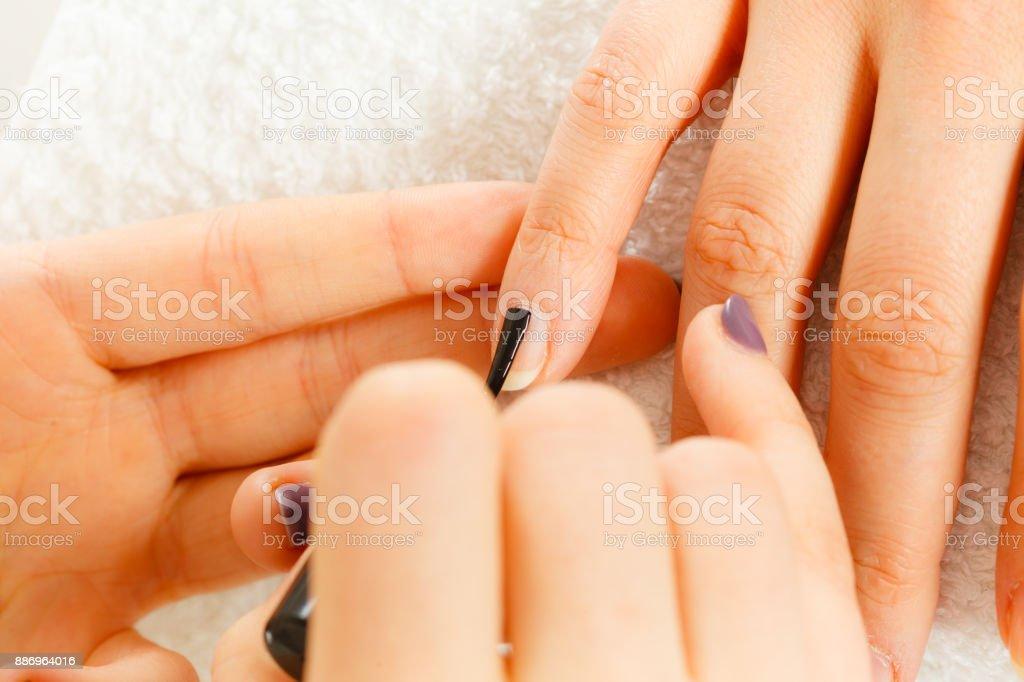Woman in beauty salon getting manicure done. – zdjęcie