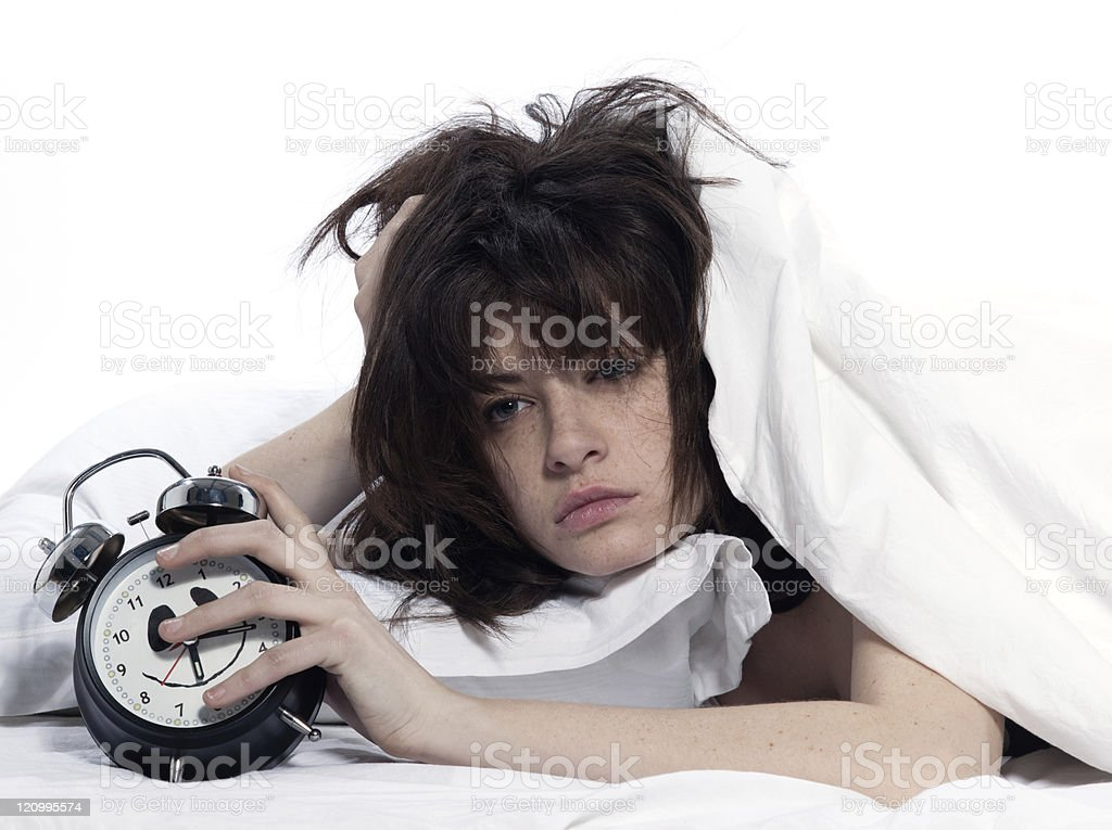 woman in bed awakening tired holding alarm clock stock photo