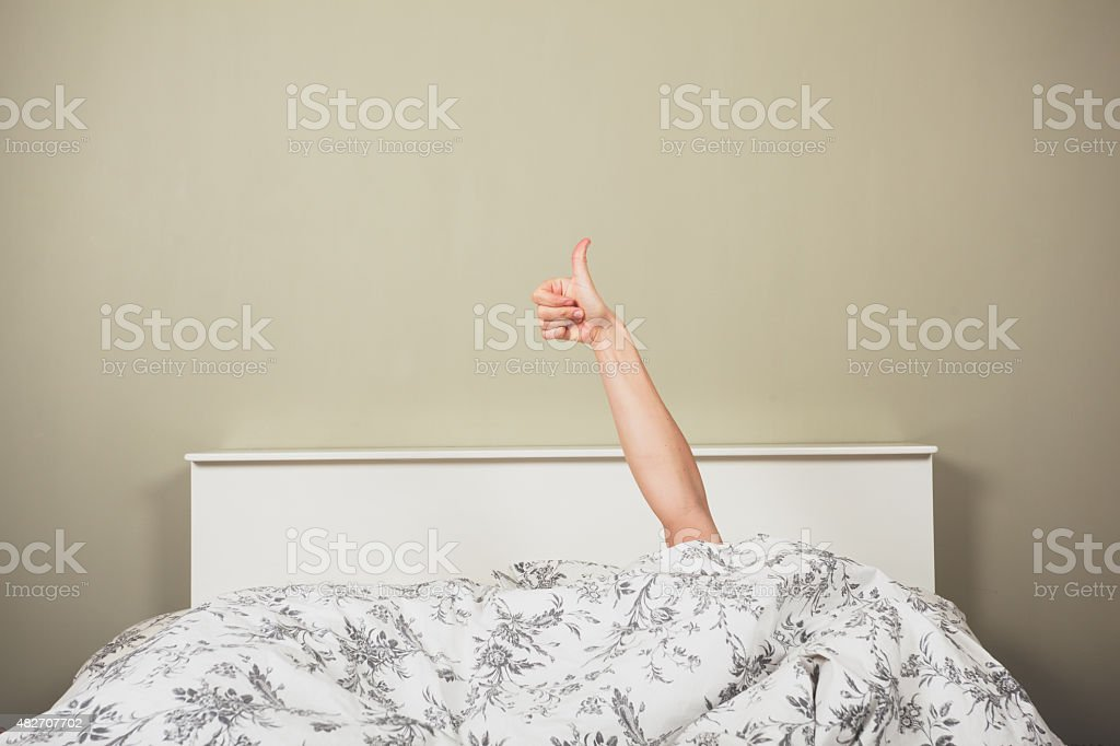 Woman in bed giving thumbs up stock photo