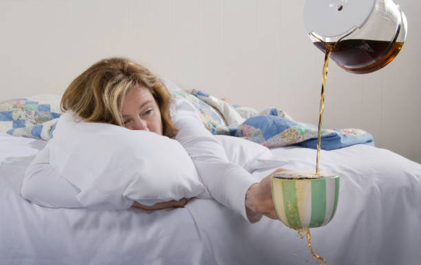 A woman in bed holding an overflowing coffee mug in her hand Exhausted woman in bed wanting more coffee. caffeine stock pictures, royalty-free photos & images