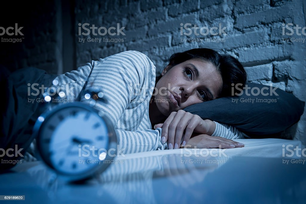 woman in bed late night trying to sleep suffering insomnia stock photo