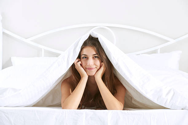 Frau im Bett, Blick in die Kamera – Foto