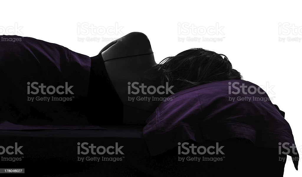 woman in bed sleeping lying on side silhouette stock photo