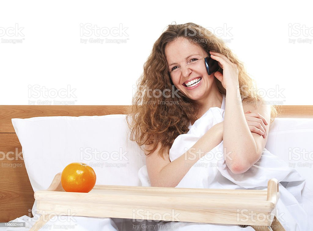 Woman in bed talking by phone with orange on tray stock photo
