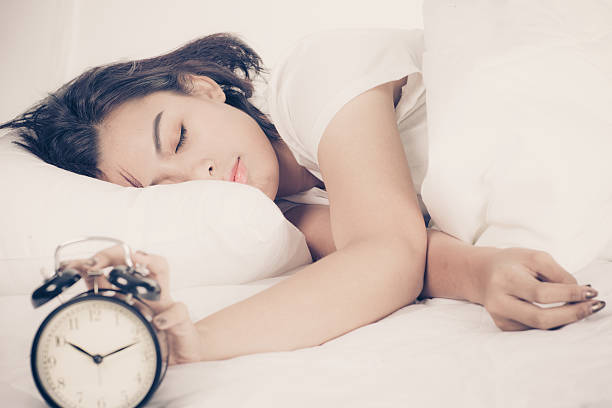 Frau im Bett zu wachen Sie mit Wecker – Foto