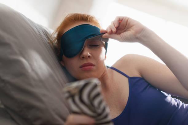 femme au lit, se réveiller à répétition de réveil portable - faire un somme photos et images de collection
