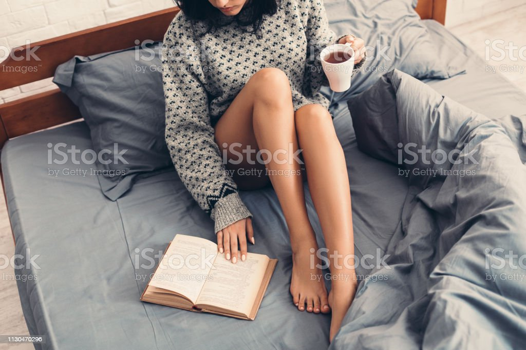 Woman in bed with book and cup of coffee - Royalty-free Adult Stock Photo