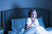 A mature woman in her 40s, woken up in bed in the middle of the night by something scary, perhaps an intruder or a nightmare. She has a frighten look on her face, hands clutching her chest.