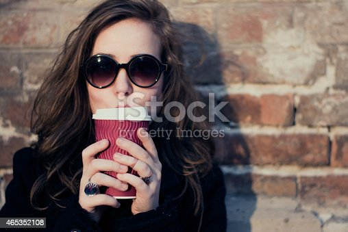 531098549 istock photo A woman in big glasses drinking a coffee 465352108
