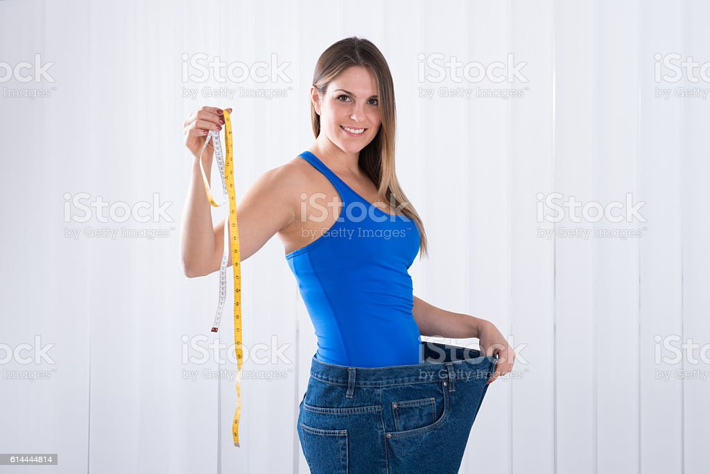 Woman In Big Jeans Holding Measuring Tape stock photo