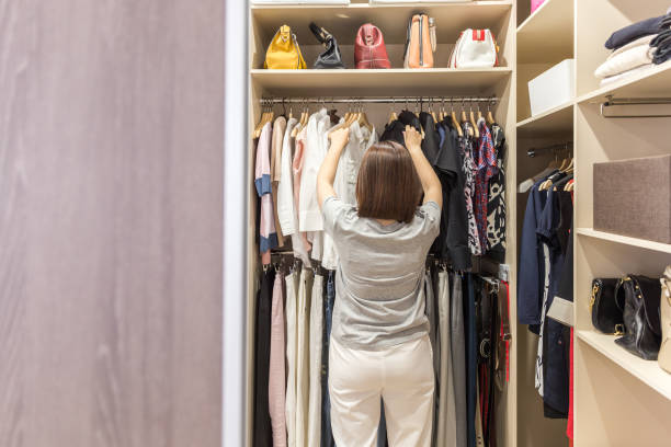 Woman in big walk in closet choosing clothes. modern wardrobe and dressing room with copy space Modern wardrobe and dressing room with copy space. Woman in big walk in closet choosing clothes. arrangement stock pictures, royalty-free photos & images