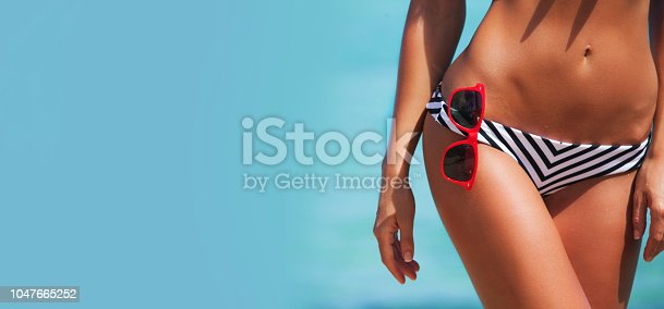 Beautiful woman body in bikini and sunglasses over blue sea background , copy space for text