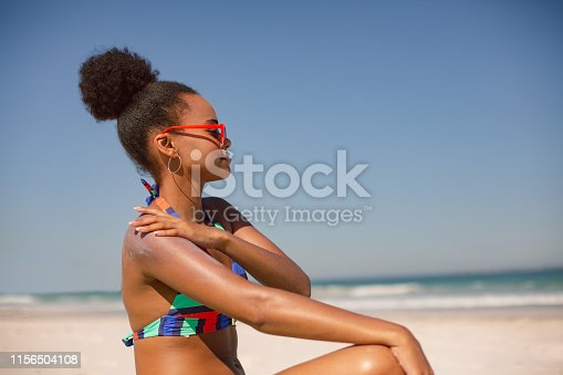 Side view of African american woman in bikini applying sunscreen lotion on shoulder at beach in the sunshine